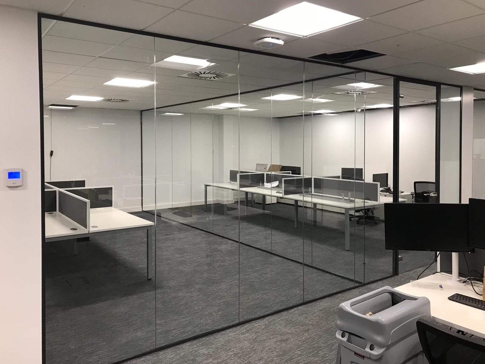 Single glazed partition with full height framed glass doors